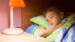barn ligger i sängen med en tänd borslampa