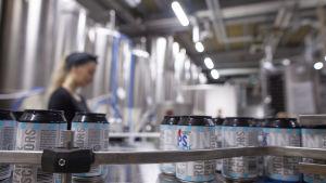 Ett ölbryggeri där ölburkar färdas på en produktionslinje. En kvinna övervakar produktionen.