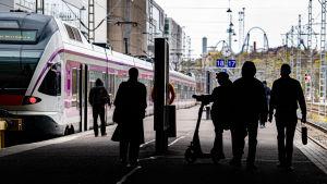 Ihmisiä Helsingin rautatieaseman junalaiturilla.
