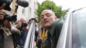 Dominic Cummings stiger in i sin bil omgiven av pressfotografer
