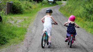 två barn cyklar på grusväg