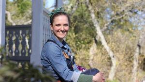 En kvinna i en blå skjota sitter på ett trappsteg och ler mot kameran. Grönskande träd i bakgrunden.