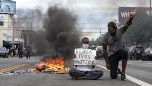 En man sitter på marken bredvis något som brinner. Han håller upp skylt där det står att svarta liv är värda lika mycket. Bredvid står en annan man på huk, han håller upp handen.