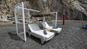 Paneler av plexiglas har satts upp runt solstolar på en strand på Santorini. Flygplatserna ute på de grekiska öarna planerar man att öppna den första juli.