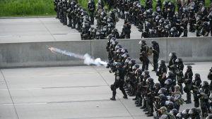 Kravallpoliser avfyrar tårgas