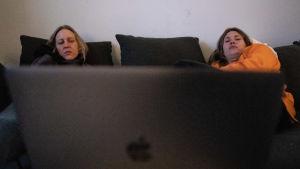 Saara Viika och Ilona Raivio tittar på en tv-serie från en laptop. 12.4 Vallgård, Helsingfors.