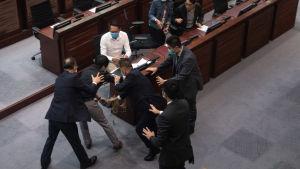 En prodemokratisk parlamentsledamot förs bort efter att ha kastat ett illaluktande gödselämne på golvet