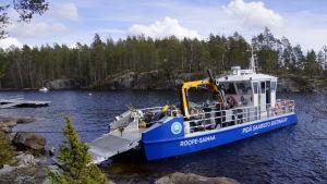 ett blått sophanteringsfartyg ligger vid en strand