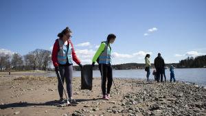 ungdomar plockar skräp på en strand