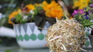 En boll av halm framför en porslinsskål med blomsterarrangemang.