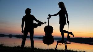Viulisti ja sellisti soittimineen poseeraavat siluetteina vasten auringonlaskua Kuhmon Kamarimusiikissa.