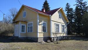 Ett gult gammalt trähus med plåttak som är hitis-rosala förskola. Soligt vårväder.