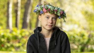 Porträtt på Greta Thunberg med blomsterkrans.