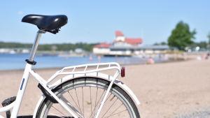 En vit cykel och i bakgrunden knipans strand i Ekenäs.