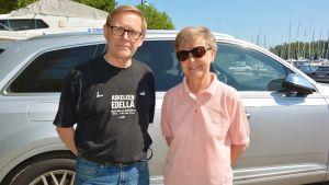 En ljushårig man klädd i svart t-skjorta, jeans och glasögon, och en ljushårigkvinna klädd i ljusröd t-skjorta, jeans och solglasögon står framför en parkerad bil.
