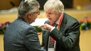 Erkki Tuomioja med fingret i vädret samtalar med Hans Wallmark.
