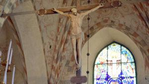 En bild på ett krucifix som hänger i taket i en kyrka, i bakgrunden syns de röda och grå detaljerna.