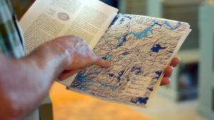 En bild på en hand som pekar på en karta över västnyland