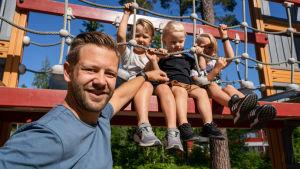 Etualalla mies nojaa kiipeilytelineeseen ja katsoo kameraan. Telineessä istuu vierekkäin kolme vaaleatukkaista 3-7-vuotiasta poikaa. Aurinko paistaa.
