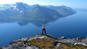 En person på toppen av ett berg vid en sjö, med fler berg på andra sidan.