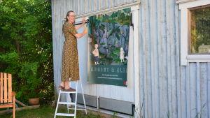 Kristiina Tiainen, en kvinna med långt ljust hår och glasögon, spikar upp en skylt för en utställning.