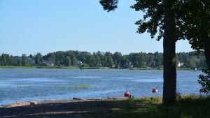 Strand, Lovisaviken och röda bojar som guppar ute i vattnet.