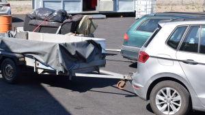 Två bilar med släpkärror fulla med avfall.