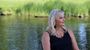 sopraano Karita Mattila istuu järven rannalla