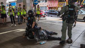 Kravallpolis griper en man i samband med demonstrationer mot en ny nationell säkerhetslag i Hongkong 1.7.2020