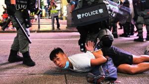 En demonstrant grips av polisen under protester mot den nya säkerhetslagen den 1 juli 2020.