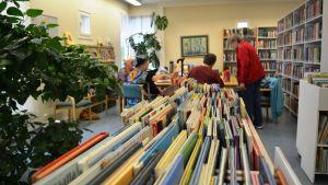 Bild inifrån ett bibliotek. I förgrunden syns böcker, i bakgrunden äldre damer kring ett bord.