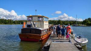 En samling människor står på en brygga bredvid en större motorbåt.