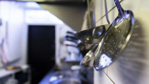 Köksredskap i rostfritt stål hänger längs en vägg i ett restaurangkök.