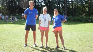 Tre ungdomar. Två har blå t-skjortor på vilka det står simlärare. Den tredje har en vit t-skjorta med texten lekledare. De har shorts och står på gräsplan. Sol och sommar.