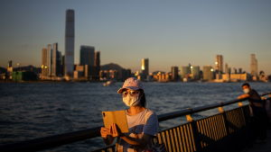 Kvinna i Hongkong med ansiktsskydd tar en selfie med skyskrapor i bakgrunden.