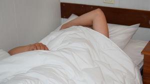 Nainen nukkuu sängyssä