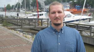En ung man i blå skjorta står framför en rad med båtar.