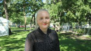 En kvinna i prickig blus står i Kuppisparken och ler.