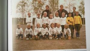 Fotbollslag med 15 barn och 3 vuxna poserar.