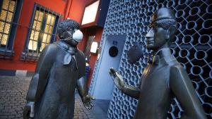 Kaksi patsasta, joista toisella maski