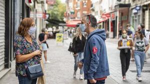 Nainen ja mies keskustelevat kadulla maskit kasvoillaan.