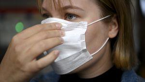 En närbild på en persons ansikte. Personen har på sig ett vitt munskydd och håller i maskens övre del med sina fingrar.