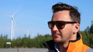 En man med solglasögon och kort mörkt hår står vid en skogsöppning. I bakgrunden syns fyra vindmöllor.