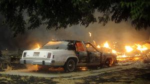 En nedbränd bil omgiven av lågor