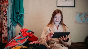 Nainen käyttää pad-laitetta saunan eteisessä.