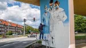 En man står under en bro och målar en graffiti på en bropelare av tre personer inom medicinska kåren och som alla tre ha munskydd.
