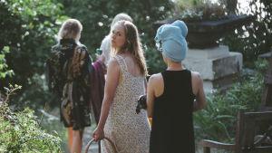 några kvinnor på väg från bastun - en av dem vänder sig om och tittar rakt in i kameran.