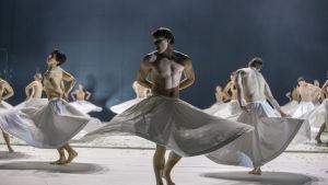 Dansare i vita kjolar på en scen.