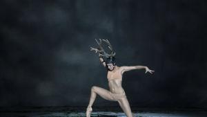 En dansare med horn på huvudet.