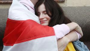 En man insvept i en rödvit flagga omfamnar en leende kvinna